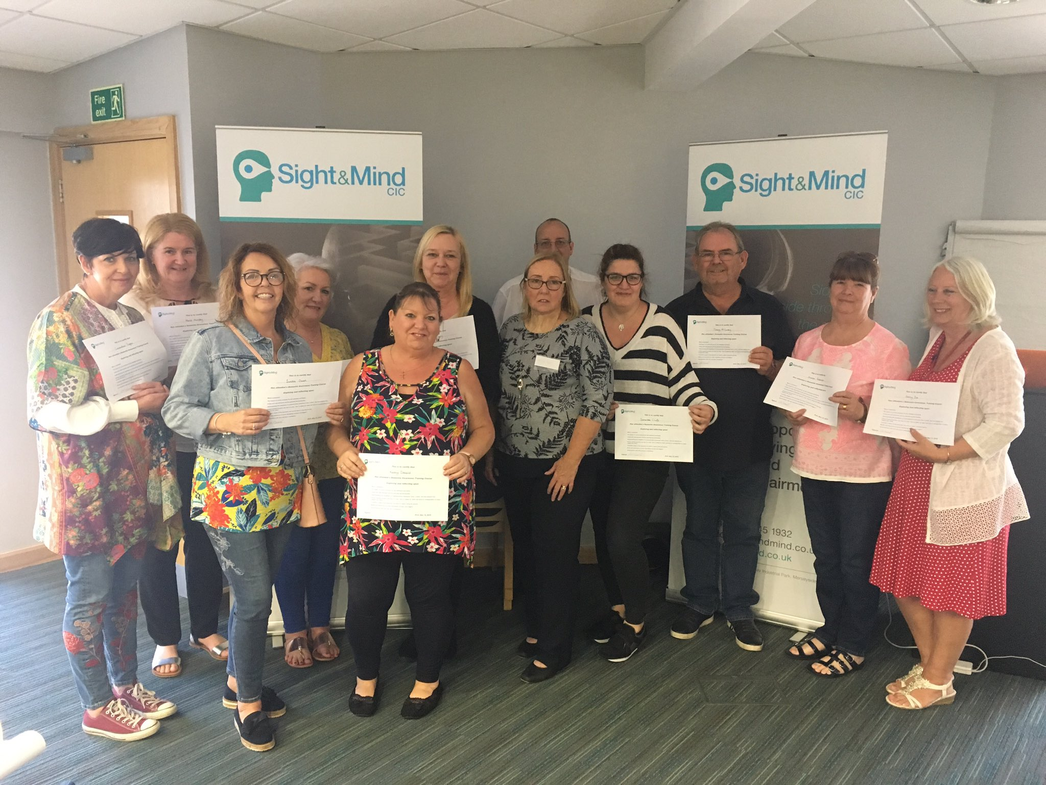 Group photo of trainees holding their training certificates